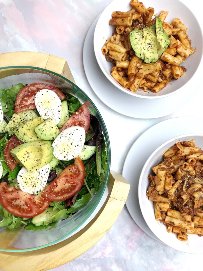 Brown Rice Pasta with Tomato Basil Marinara and Organic Ground Beef. And a Side Salad with Spring Mix, Avocado, Tomato, Cucumber, Cilantro and a Boiled Egg.