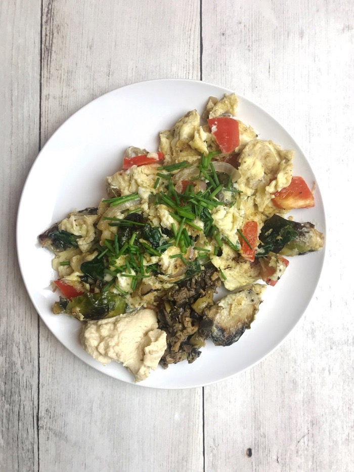 Drool-Worthy Egg Scramble: Spinach, Red Bell Pepper, Onion, Brussels sprouts, and two eggs. Topped with Chives, Olive Tapenade and Hummus.