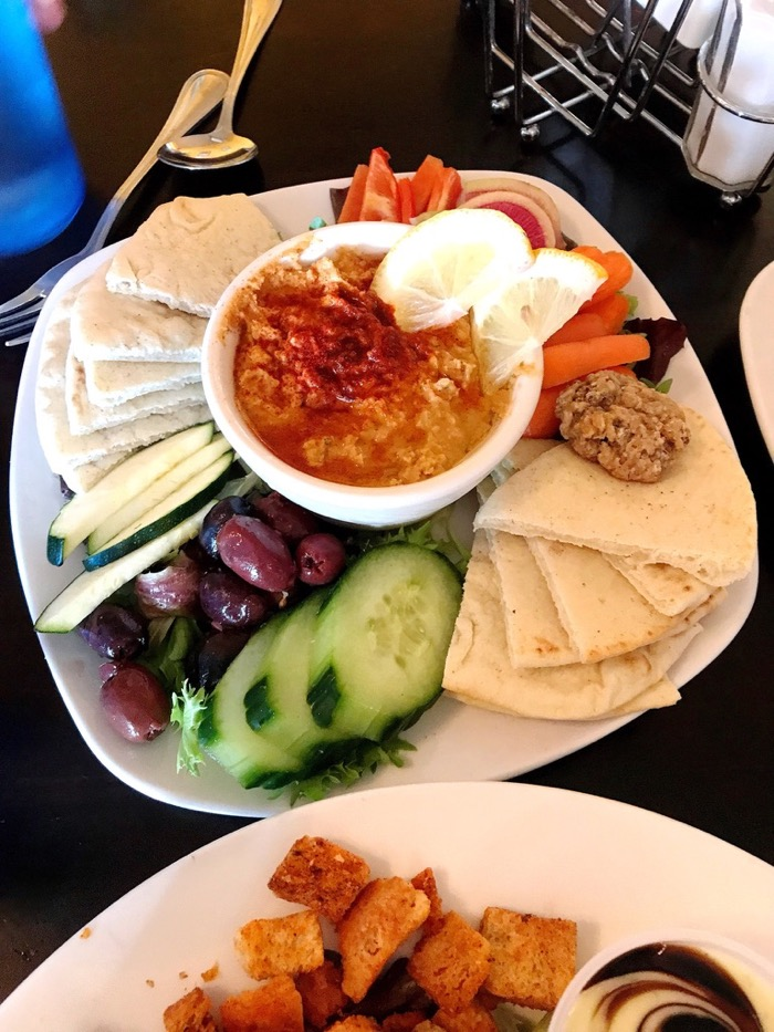 A Hummus Plate with Cucumbers, Olives, Tomatoes, and Pita for the Table at Süp in Reno. So Fresh and Tasty.