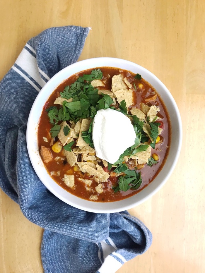 Chicken Enchilada Soup with Tortilla Chips, Sour Cream and Cilantro on Top. The Perfect Crockpot Meal with Leftovers.