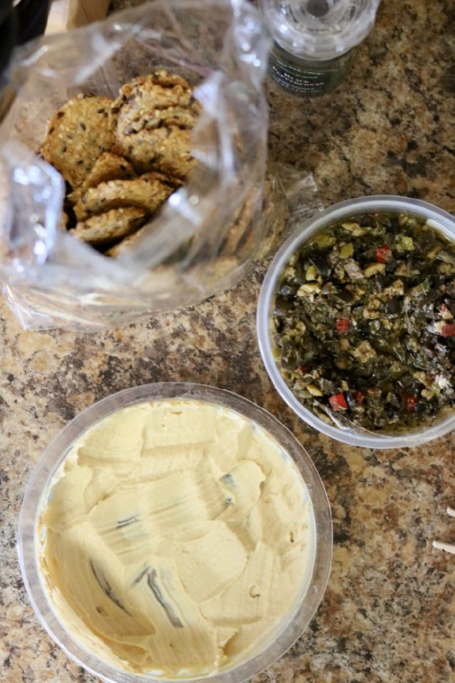 Quick snack idea while you heat up dinner: Mary's crackers with hummus and olive tapenade.