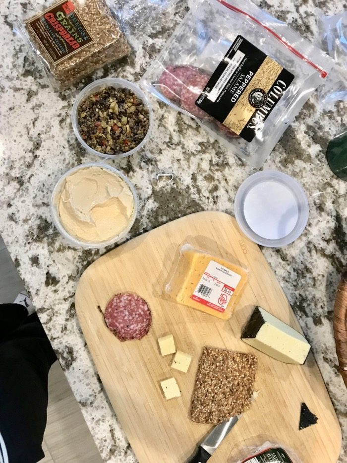 Savory Afternoon Snack Board You Can Make at Home: Salami, Crackers, Cheese, Hummus and Olive Tapenade.