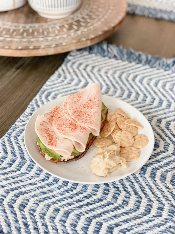 Daily Eats | Open faced sandwich with toasted sourdough, hummus, avocado, and turkey and paprika sprinkled on top. Brown rice crackers and hummus on the side!