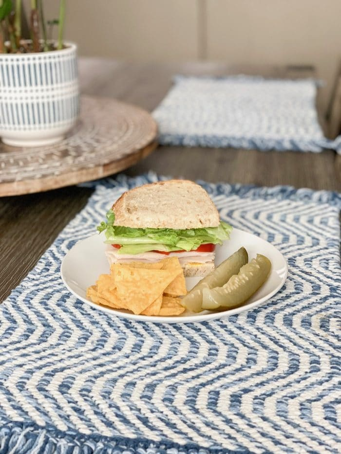 Turkey club on sourdough with two pickle spears and kettle brand chips