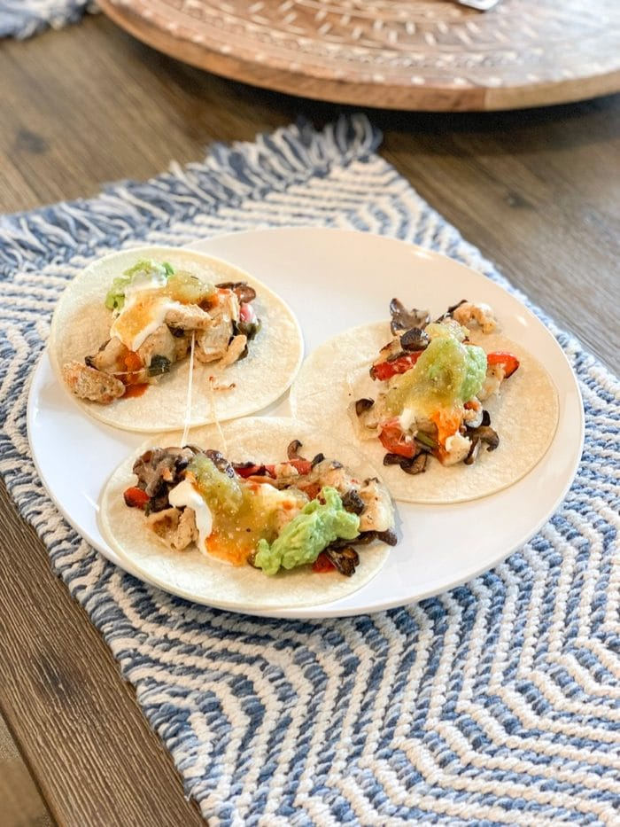 Daily Eats | Chicken fajitas with mushrooms, peppers, cheese and . topped with guacamole, sour cream, and salsa verde.