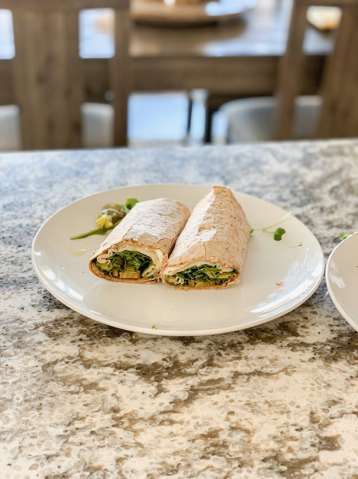 A wrap on a sprouted grain tortilla with cream cheese, pesto, turkey, provolone, arugula, sprouts, pickles, deli jalapenos and sliced pepperoncini's.