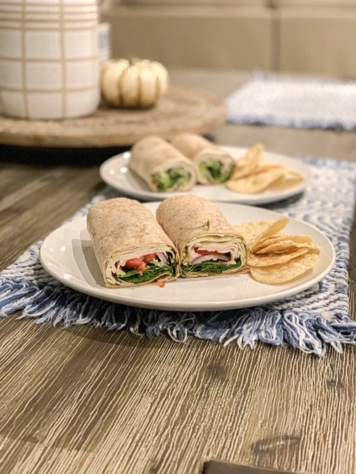 Wraps with sprouted grain tortillas (so good and from Trader Joe's), a little cream cheese, pesto, spinach, arugula, tomato, onion, sprouts, turkey, provolone, and sliced deli jalapeños. Plus a few chips on the side.