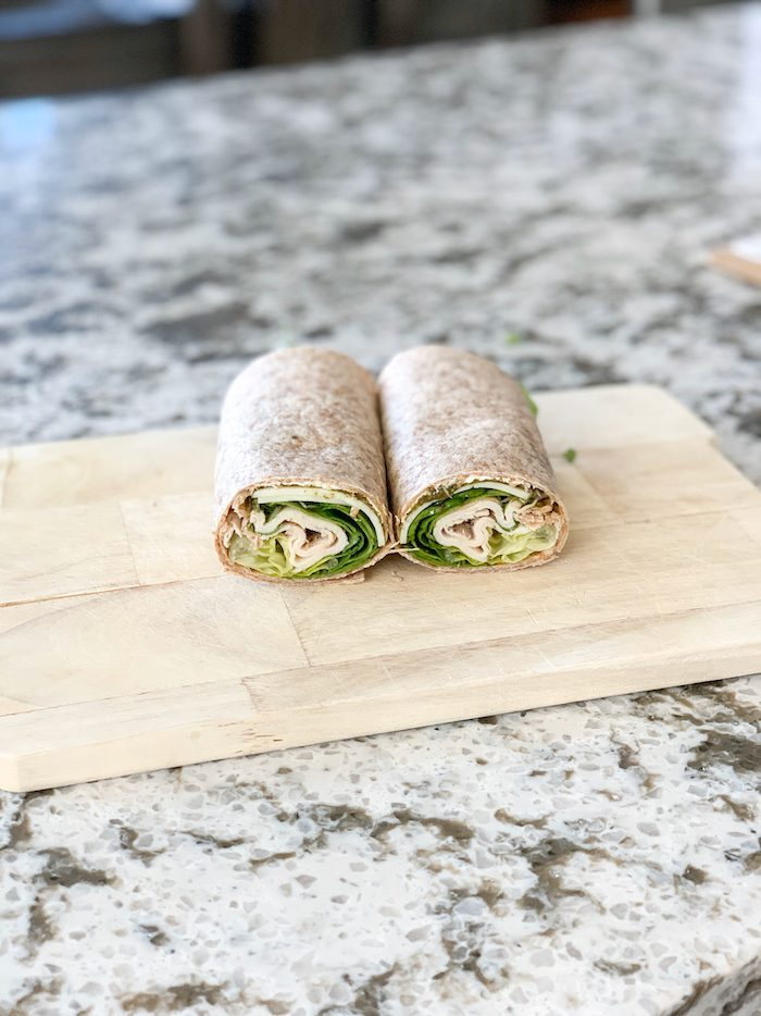 A turkey wrap with a sprouted grain tortilla, mayo, provolone cheese, turkey, avocado, and arugula.