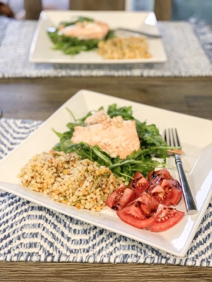 Salmon baked with olive oil, butter, lemon and garlic... on a bed of arugula drizzled with olive oil and sprinkled with sea-salt, tomatoes, and harvest grains