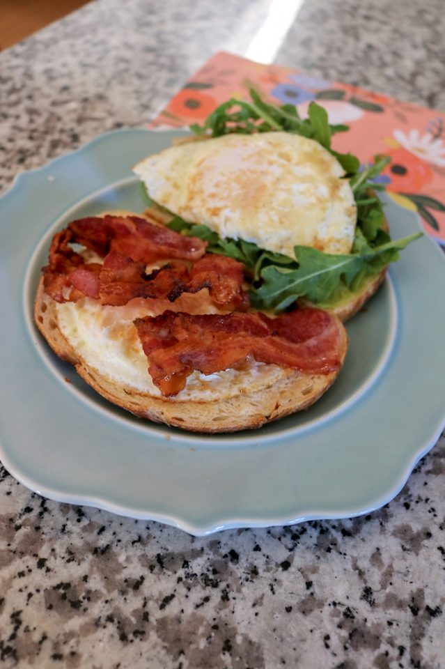 """Breakfast BLAT: two slice of sourdough, two eggs over medium, two slices of bacon, a """"tiny"""" avocado, and arugula."""