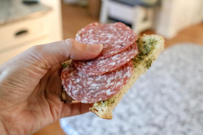 Half a slice of sourdough with pesto and salami.