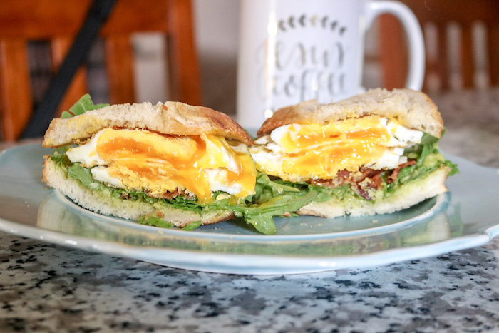 Sourdough toast, over-medium eggs, avocado, bacon, and arugula
