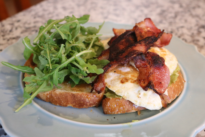 dinner - a breakfast sandwich with bacon, egg, avocado, and arugula.