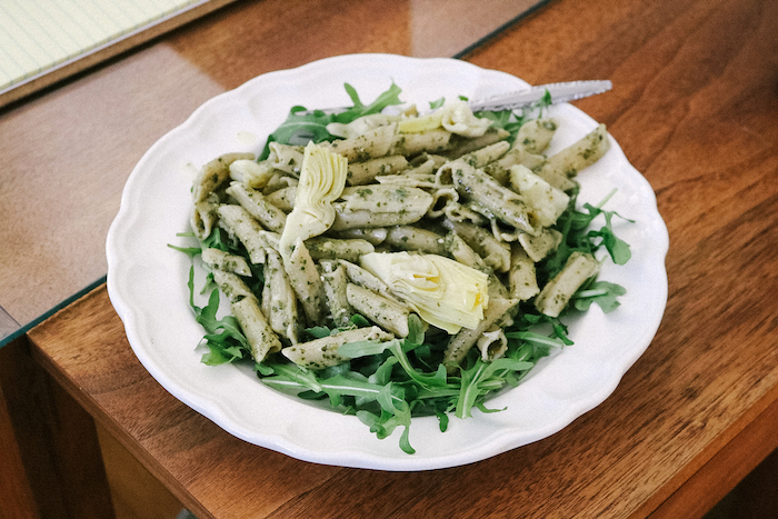 Lunch: brown rice penne noodles, pesto, arugula, and marinated artichoke hearts.