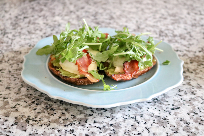 Two slices of sourdough, two eggs, two slices of bacon, and arugula