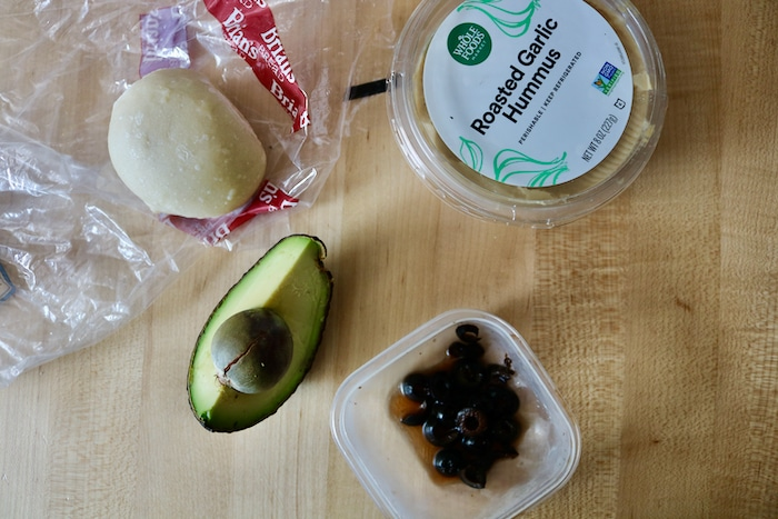 Sourdough bread roll, avocado, hummus and olives