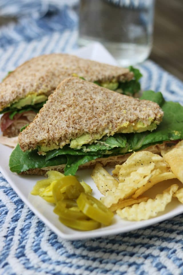 Lunch: a sandwich with steamed deli meat, mayo/mustard, avocado, and lettuce on Ezekiel. A few crinkle cut chips on the side, plus some pepperoncinis and pickled jalapeños.