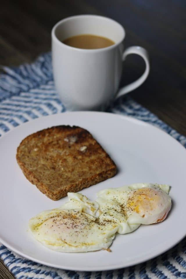 Made a cozy breakfast at home: coffee, a slice of toasted Ezekiel and two eggs over-medium.